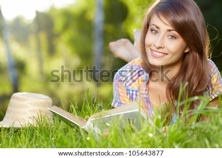 female student lying on the grass with a books