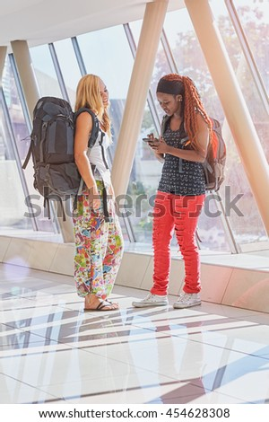 2 female travelers in airport hallway checking phone