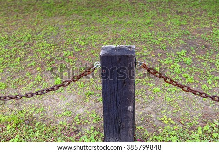 fence made of cracked wooden beams and rusty iron chain