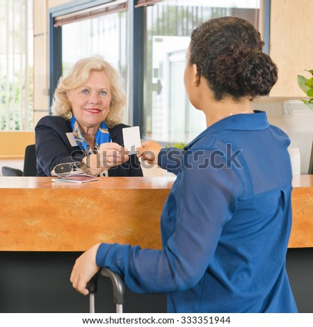 File name:     Receptionist helping a guest at a hotel, handing out the electronic key card for their room  - stock photo