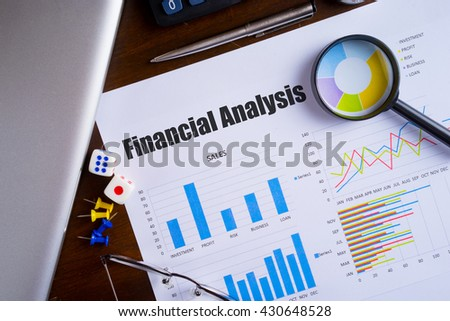 """""""Financial Analysis"""" text on paper sheet with magnifying glass on chart, dice, spectacles, pen, laptop and blue and yellow push pin on wooden table - business, banking, finance and investment concept - stock photo"""