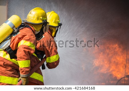 2 firefighters spraying water fire fighting operation - stock photo