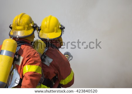 2 firemen spraying water in fire fighting with fire and dark smoke background - stock photo