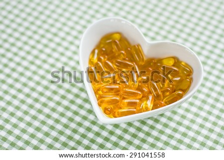 fish oil capsules in a bowl - stock photo