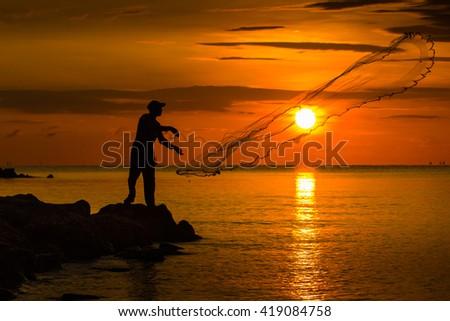 fisherman casting a net. - stock photo