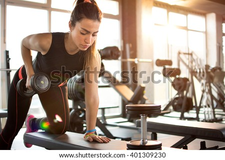 Fitness girl lifting dumbbell in the morning. - stock photo