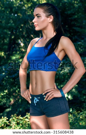 Fitness sporty woman showing her well trained body. Strong abs showing        - stock photo