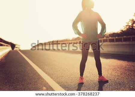 fitness young woman runner standing with her hands on hips on sunrise road