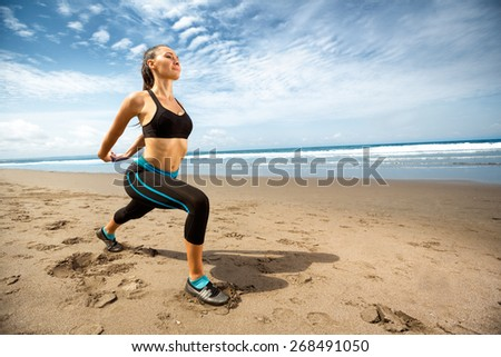 Fitness young woman stretching on beach - stock photo
