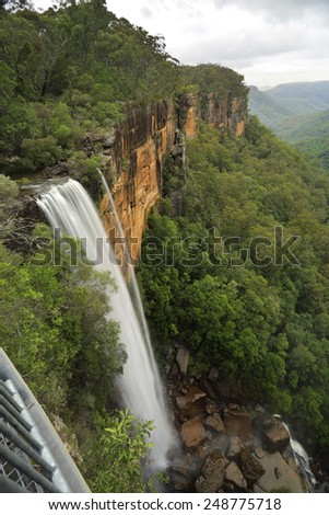 Fitzroy Falls from the grated balcony lookout at the top of the escarpment with a  perspective capturing the first of the spectacular falls iover sheer vertical cliffs to the valleys below.   - stock photo