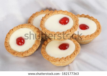 five cherry bakewell cakes on a white cloth