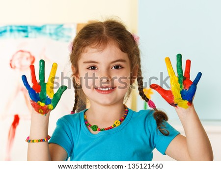Five year old girl with hands painted in colorful paints ready for hand prints - stock photo
