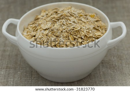 flakes in a white bow  wooden spoon lie on canvas - stock photo