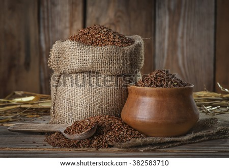 Flax seeds, Linseed in a bag and a bowl, spoon on the old wooden background - stock photo