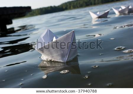 fleet of origami handmade paper boats - stock photo