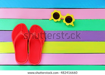 Flip flop with sunglasses on colorful wooden background