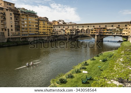 FLORENCE - April 23rd 2015. View of medieval stone bridge Ponte Vecchio and the Arno River with rowers in Florence, Tuscany, Italy. Florence is a popular tourist destination of Europe.