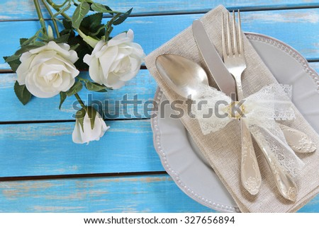 Flowers,Plate and cutlery on a wooden table - stock photo
