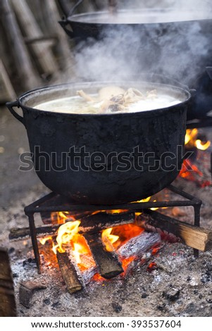 Food prepared in old cast iron outside - stock photo