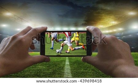 Football fan removes the football game on mobile phone - stock photo