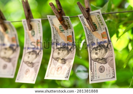 Four hundred dollar bills hanging on a clothesline  - stock photo