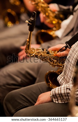 Fragment of a saxophone in the hands of a musician in a jazz orchestra