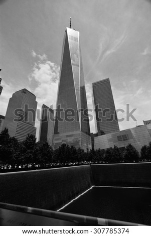 Freedom Tower New York/ One World Trade Center/ New York, USA - June 11, 2015: Freedom Tower, New York City, One World Trade Center with 9-11 memorial park in foreground on sunny day - stock photo