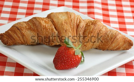 fresh baked butter croissant wit a ripe strawberry                               - stock photo