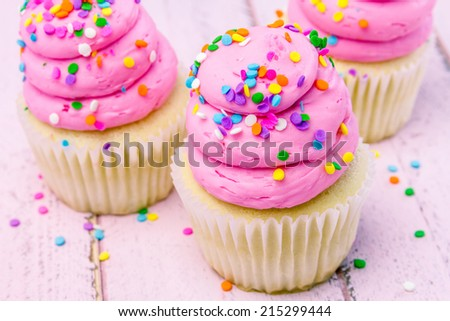 3 fresh baked vanilla cupcakes with pink swirled strawberry frosting topped with colorful sprinkles