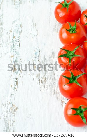 Fresh cherry tomatoes on the wooden background. Selective focus - stock photo