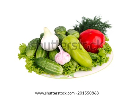 Fresh garden vegetables on plate isolated on white