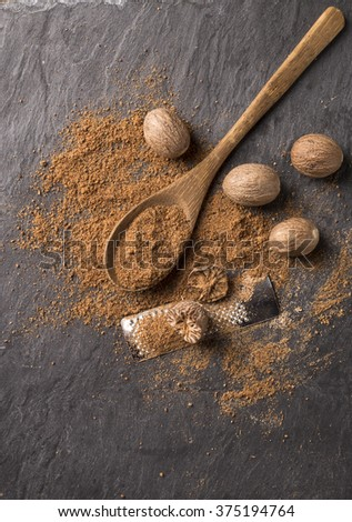 fresh grated nutmegs and whole ones over black background - stock photo