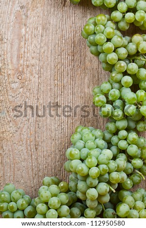 fresh green grapes on wooden background with copyspace - stock photo