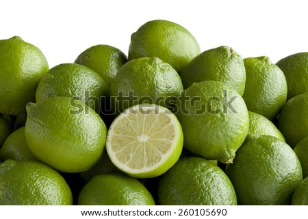 Fresh green limes and a half one - stock photo