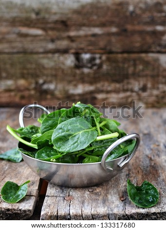 fresh green spinach in to the bowl - stock photo