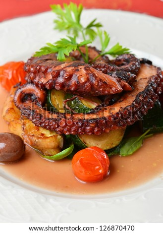 Fresh grilled octopus with olives, potato, tomatoes, zucchini, vegetable and parsley