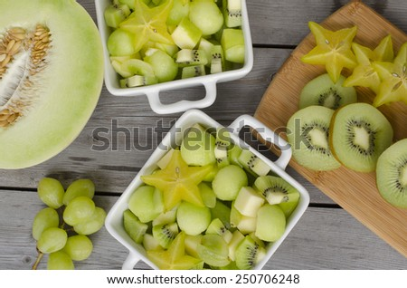 fresh healthy fruit salad and ingredients on wooden background - stock photo