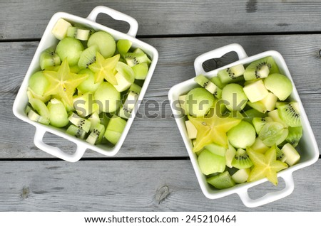 fresh healthy fruit salad on wooden background - stock photo