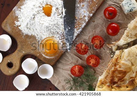 Fresh home baking . Pie with fish or vegetables homemade. eggs, cherry tomatoes, wheat flour, cheese, top view, closeup. Ingredients for baking. - stock photo