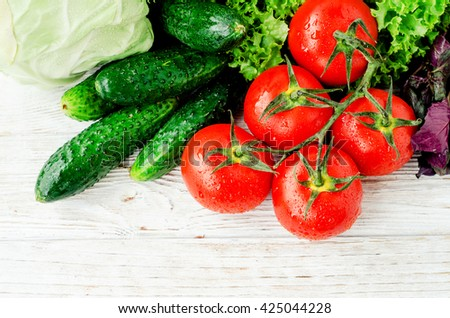 Fresh juicy ripe summer useful vegetables and greens, red tomatoes , cucumbers , cabbage , lettuce , basil , parsley , dill and salt and spices on a wooden background - stock photo
