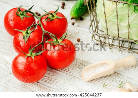 Fresh juicy ripe summer useful vegetables and greens, red tomatoes , cucumbers , cabbage , lettuce , basil , parsley , dill and salt and spices on a wooden background