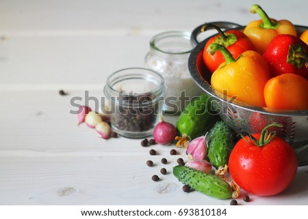 Fresh organic vegetables: cucumbers, tomatoes, sweet peppers, garlic on a wooden table, light background