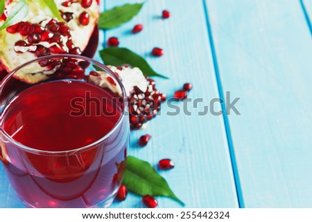 fresh pomegranate juice and ripe pomegranate seeds on a blue wooden background.health and diet food. copy space for you text - stock photo