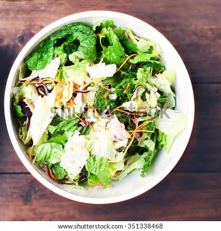 Fresh spring salad with rucola, red onion and lettuce leaves in white bowl on wood background