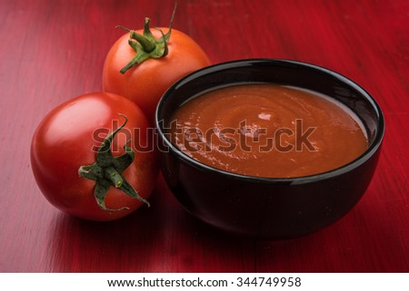 2 fresh tomato with tomato paste or puree or ketchup in black bowl, isolated on red wooden background - stock photo