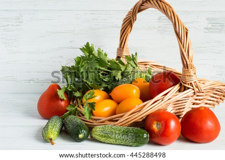 Fresh vegetables in a wicker basket on a light wooden background. - stock photo