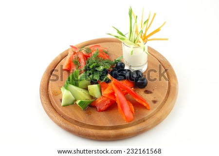 Fresh vegetables on a wooden plate with sauce on a white background - stock photo