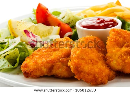 Fried chicken nuggets, French fries and vegetables
