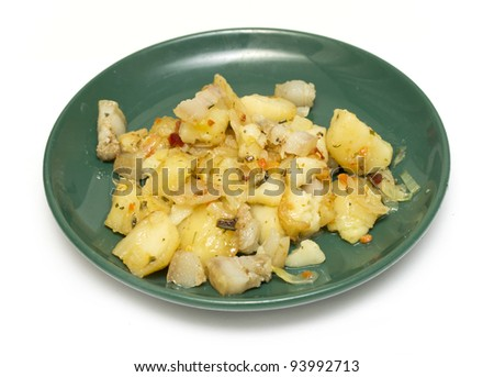 fried potatoes on a plate of green