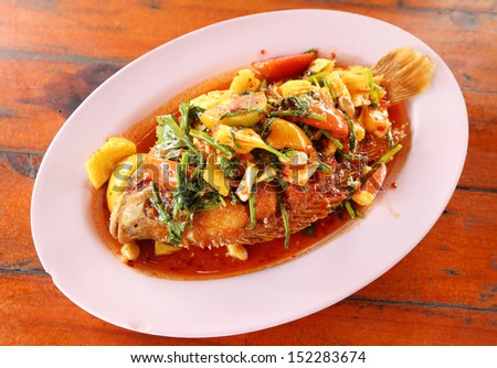 Fried ruby fish topped with sweet,sauer and hot sauce on dish - stock photo